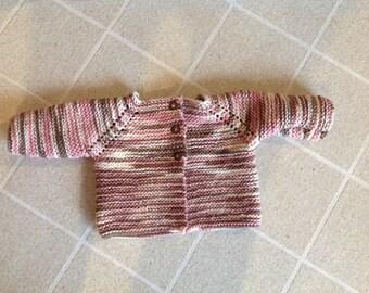 Newborn hand knitted girl's sweater.