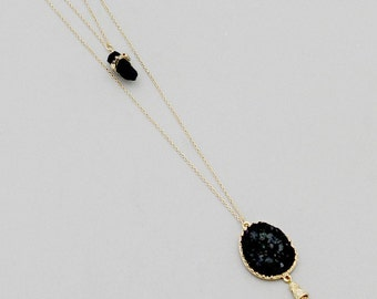 Double layer golden pendant with simulated black druzy stones finished off with metallic tassel.