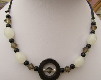 White, brown and black necklace with wooden ring detail