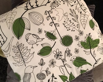 White cushion, leaves & birds print in black and green