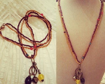 Bronze colored beaded necklace with dangle charms