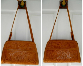 50s-60s tooled leather crossover bag. Made in Mexico, one side floral, one side Aztec-Myan, sturdy, lots of pockets, Adjustable strap.