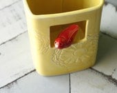 Square vase in marigold with red bird perched in window