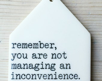 porcelain wall tag screenprinted text remember, you are not managing an inconvenience. you are raising a human being. -kittie frantz