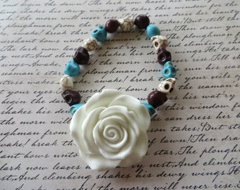 Stretch Bracelet With Large White Resin Rose And Multi Colored Howlite Skull Beads