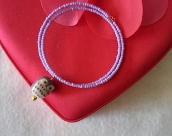 Purple porcelain owl and purple seed bead memory wire bracelet.
