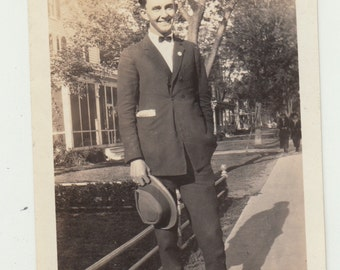 Vintage/ Antique sephia Photo of a happy man in suit with bow tie holding a hat