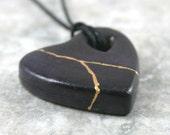 Dark blue faux kintsugi (kintsukuroi) broken heart pendant with gold repair in bisque porcelain on black cotton cord - OOAK