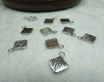 Little silver tags with loops for stamping or bails