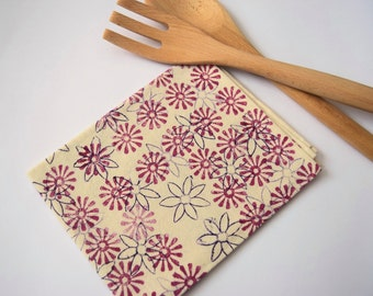 Hand block printed tea towel in a 100% off white natural cotton with a flowery design in purple & pink