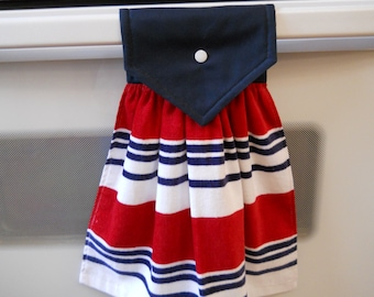 Hanging kitchen towel with colorful blue, red and white stripes on the front.