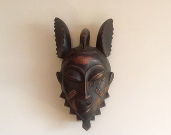 Vintage West African tribal mask, serene expression with mouse like ears