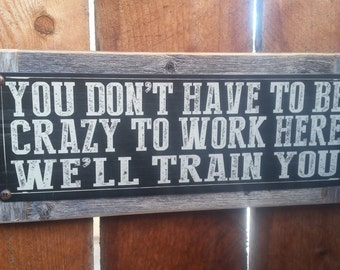 """Recycled wood framed """"You Dont Have to be Crazy to Work Here"""" street sign"""