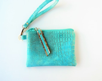 Turquoise embossed leather, lightly dusted with gold.  Leather wristlet or clutch.