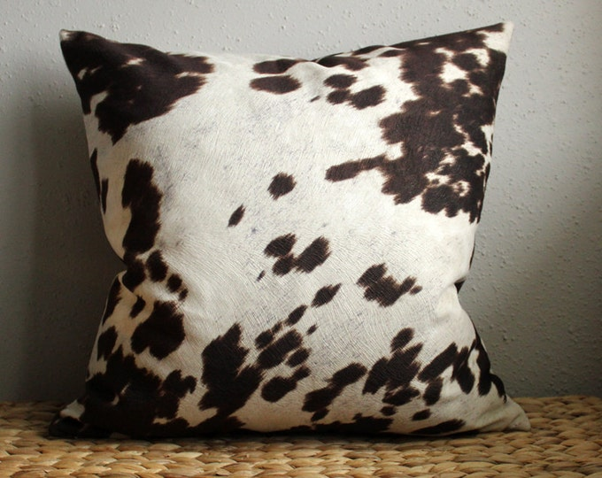 brown and white cow print pillow