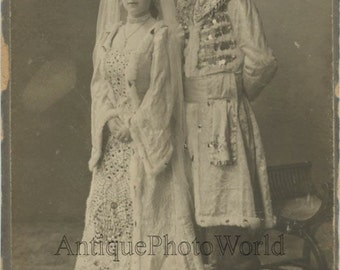 Couple in fantastic elaborate Russian costumes antique ethnic photo