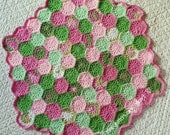 Hand made crocheted hexagonal shaped baby blanket in beautiful shades of pink and green