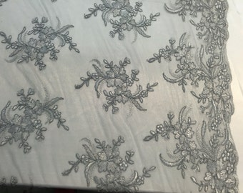 Gray hibiscus flower design embroider and corded on a mesh lace fabric -yard