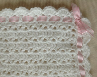 white crocheted baby blanket with pink gingham ribbon