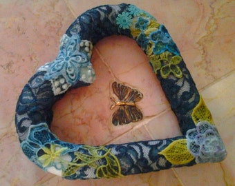 Heart shaped decoration with lace appliques .