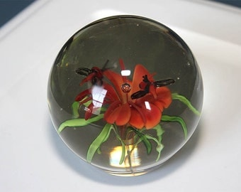 Orange flowers with bee paperweight.