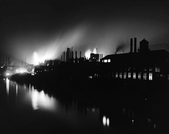 Iron works in Pittsburgh - night scene on riverside. Reproduction of vintage photograph