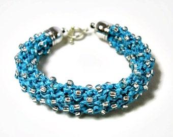 Knitted bracelet with Toho beads in shiny blue ribbon yarn, knit design, statement bracelet, Christmas gift