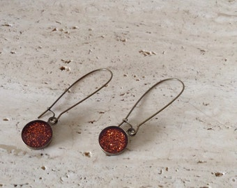 Kidney shaped, burnt orange glitter drop earrings.