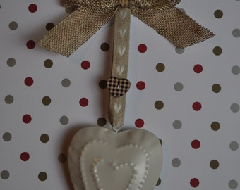 Metallic beige heart hanging decoration embellished with ribbons and a button.