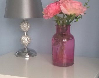 A  pink vase with peony pink flowers and a pink rose