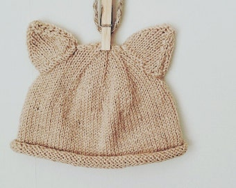 Hand knitted beige 'cat' style bonnet.
