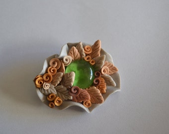 Soft muted yellow gold and grey flowery polymer clay brooch with a green glass stone
