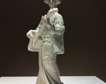 Figurine of asian woman playing instrument