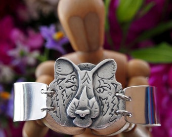 A gorgeous hand made fine silver tiger head on a wide sterling silver bangle...