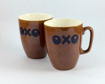 OXO coffee mugs or tea mugs. Vintage brown ceramic with dark blue logo. For home use, coffee house, café, restaurant.