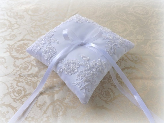 White wedding ring pillow decorated with white lace flowers and beads embroidery.