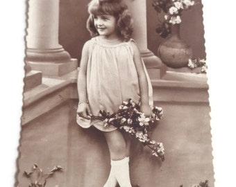 Vintage Postcard . Postcard of a Young Girl with flowers .