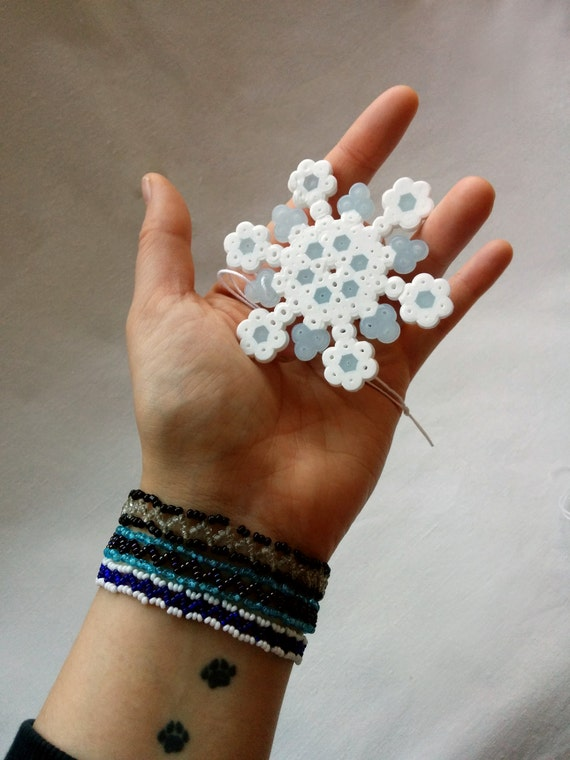 Pixelated snowflake, Christmas ornaments made out of white and blue glow-in-the-dark Hama Midi beads