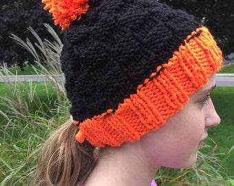 Hand knit orange & black hat with pony tail hole