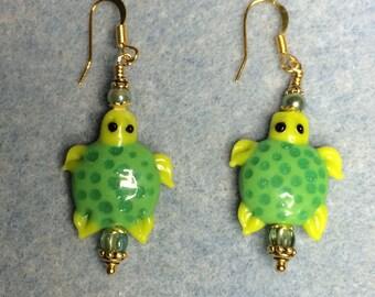 Green lampwork turtle bead dangle earrings adorned with green Czech glass beads.