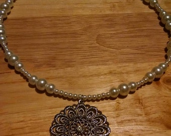 White faux pearl necklace with flower pendant.