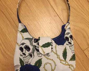 Smaller top handled bag, white featuring skulls and blue roses