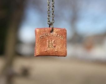 metallic postage stamp necklace