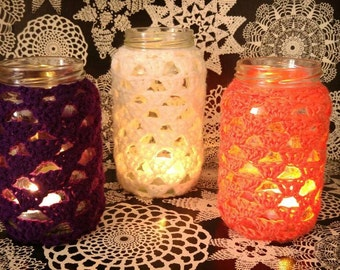 Set of three crochet recycled jar candle lanterns purple cream and orange.
