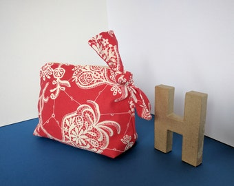 Medium sized cosmetics bag, with a large bow on the zipper