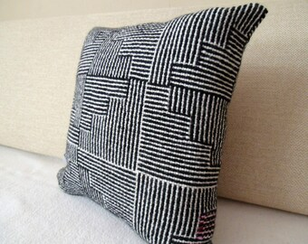 black and white sofa cushion with a blur of pink