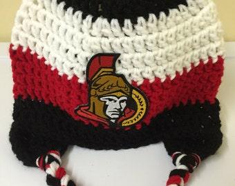 Senitors crochet hockey team hat for adult.  Black white and red ottawa hockey hat.