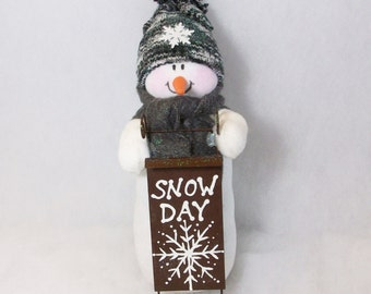 stuffed snowman table top decoration: It's a snow-day with a sled
