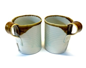 Set of tall mugs with ribbon handle made from porcelain.