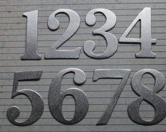 2 1/2 inch tall Numbers 1-12 silver brushstroke matte foil cardstock on top of chipboard diecuts great for wedding table numbers
